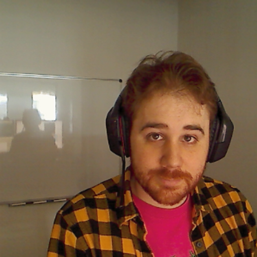 Picture of a bearded, red-haired man looking into the camera while wearing headphones and a yellow-and-black plaid shirt.