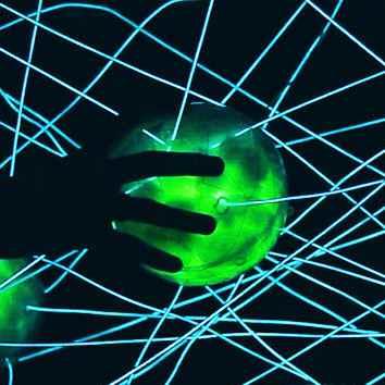 A hand touching a green-lit ball