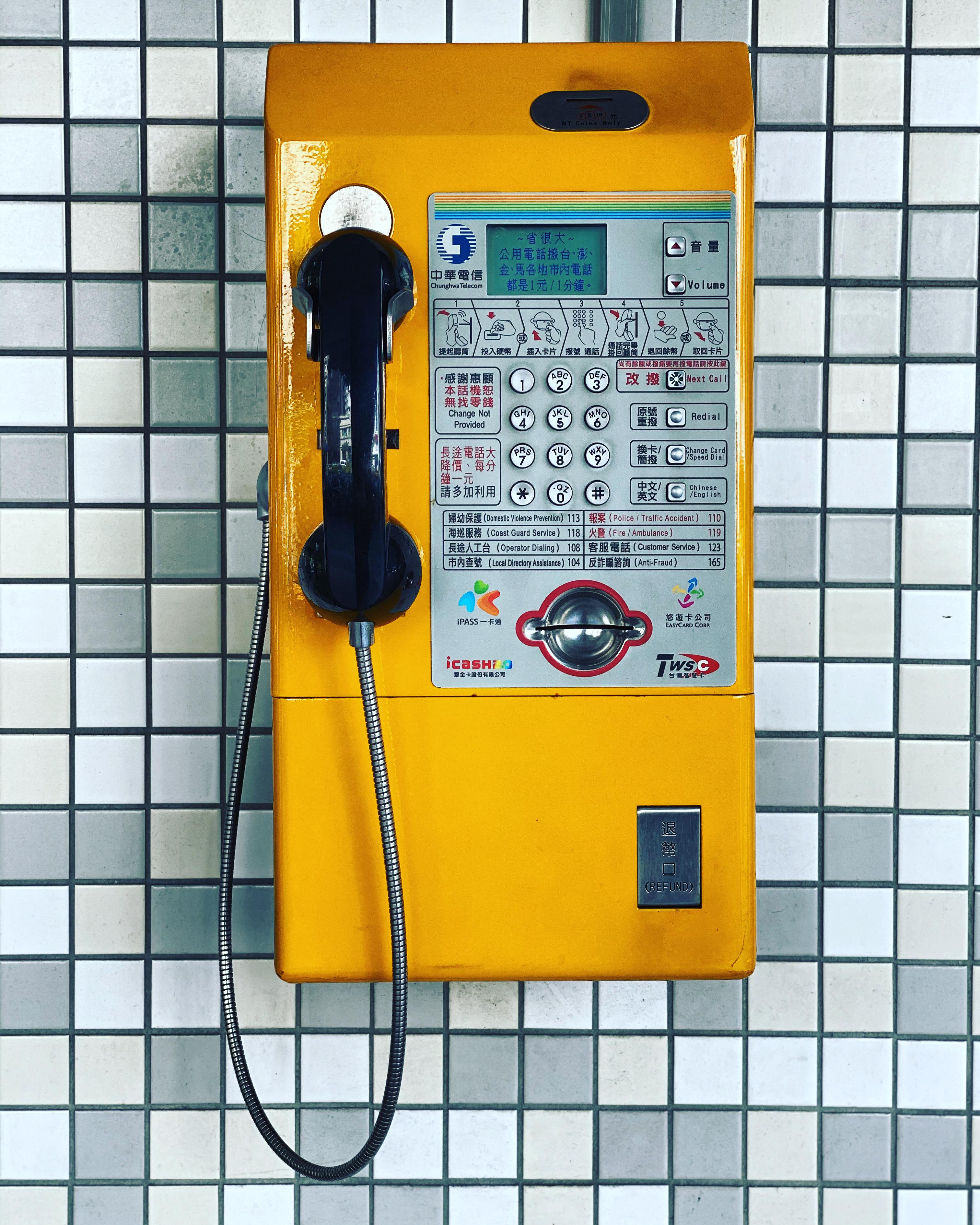 Bright yellow public payphone