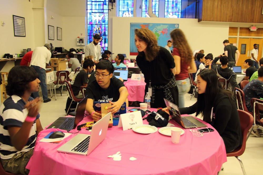 photo of me at a table of kids talking during a high school hackathon
